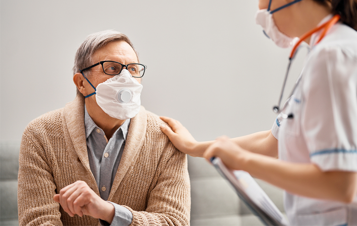 Nurse wearing a mask resting a comforting hand on the shoulder of an older man, also wearing a mask.