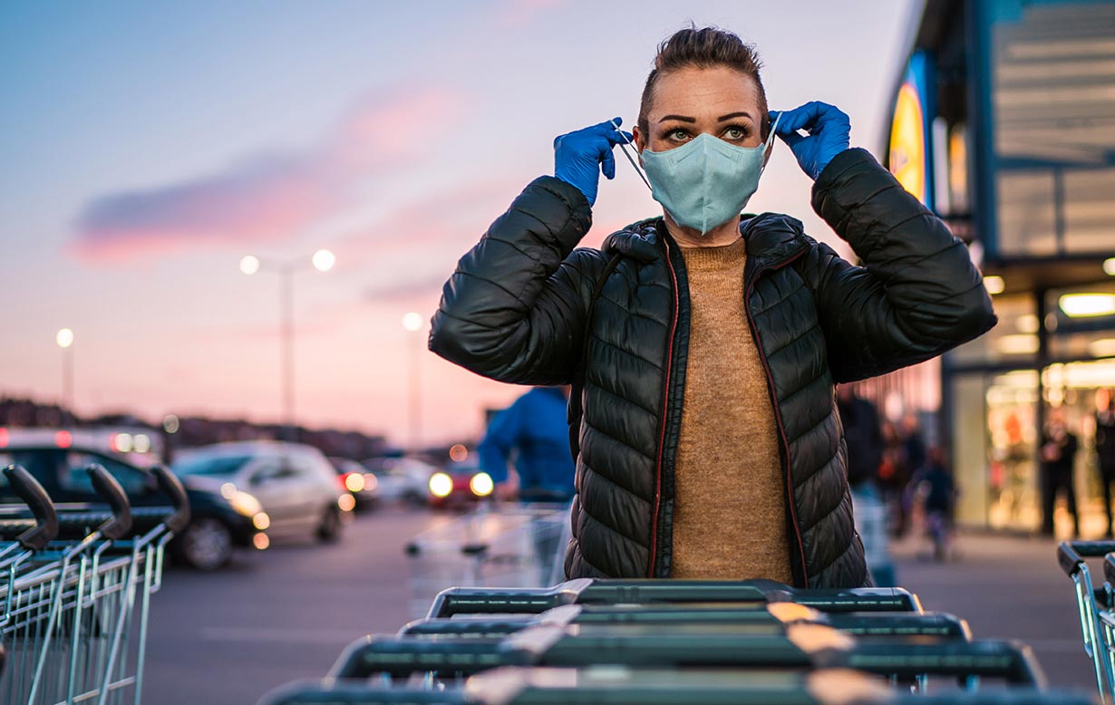 Woman in front of grocery store, putting on her face mask PPE.