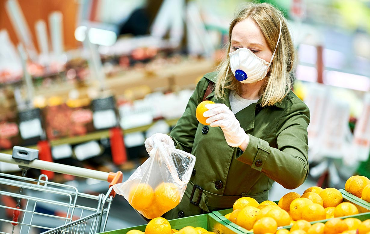 Woman wearing filtering facepiece (FFP) respirator/mask and gloves while grocery shopping.