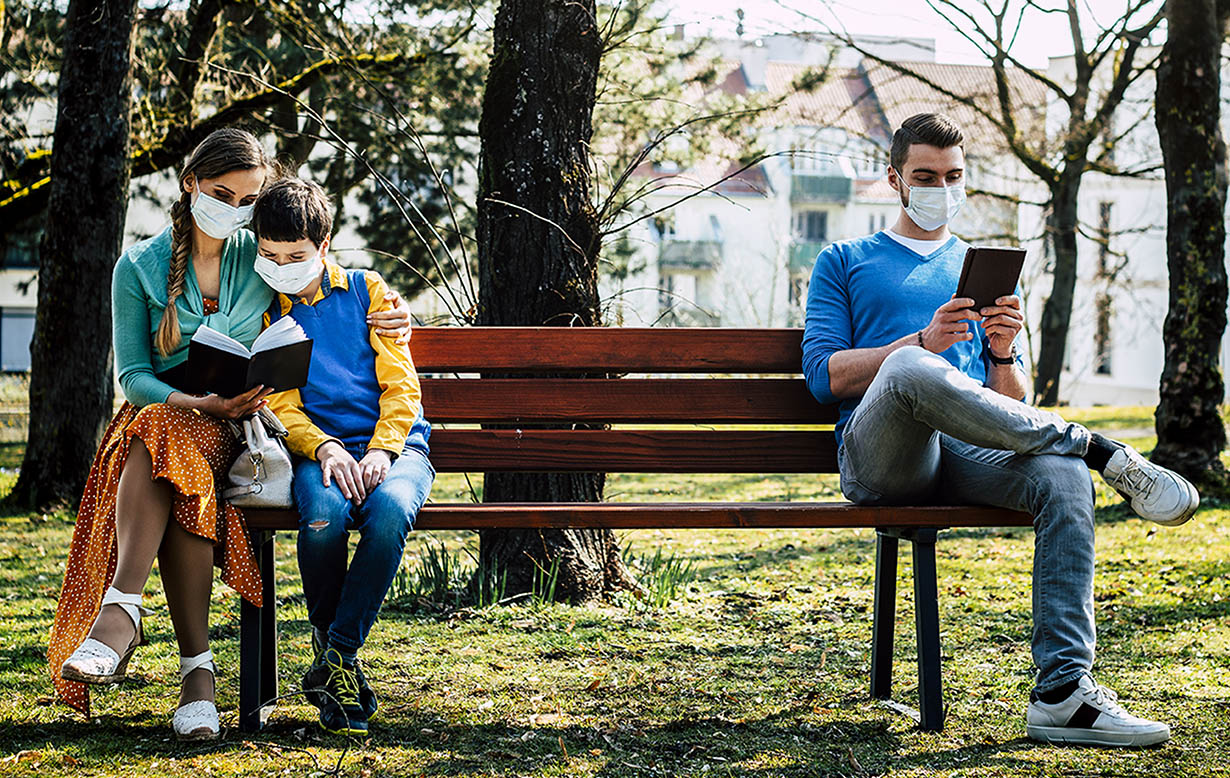 Woman with child (wearing masks) reading a book sitting on a bench 6 feet away from another gentleman (also wearing a mask) looking at his tablet.