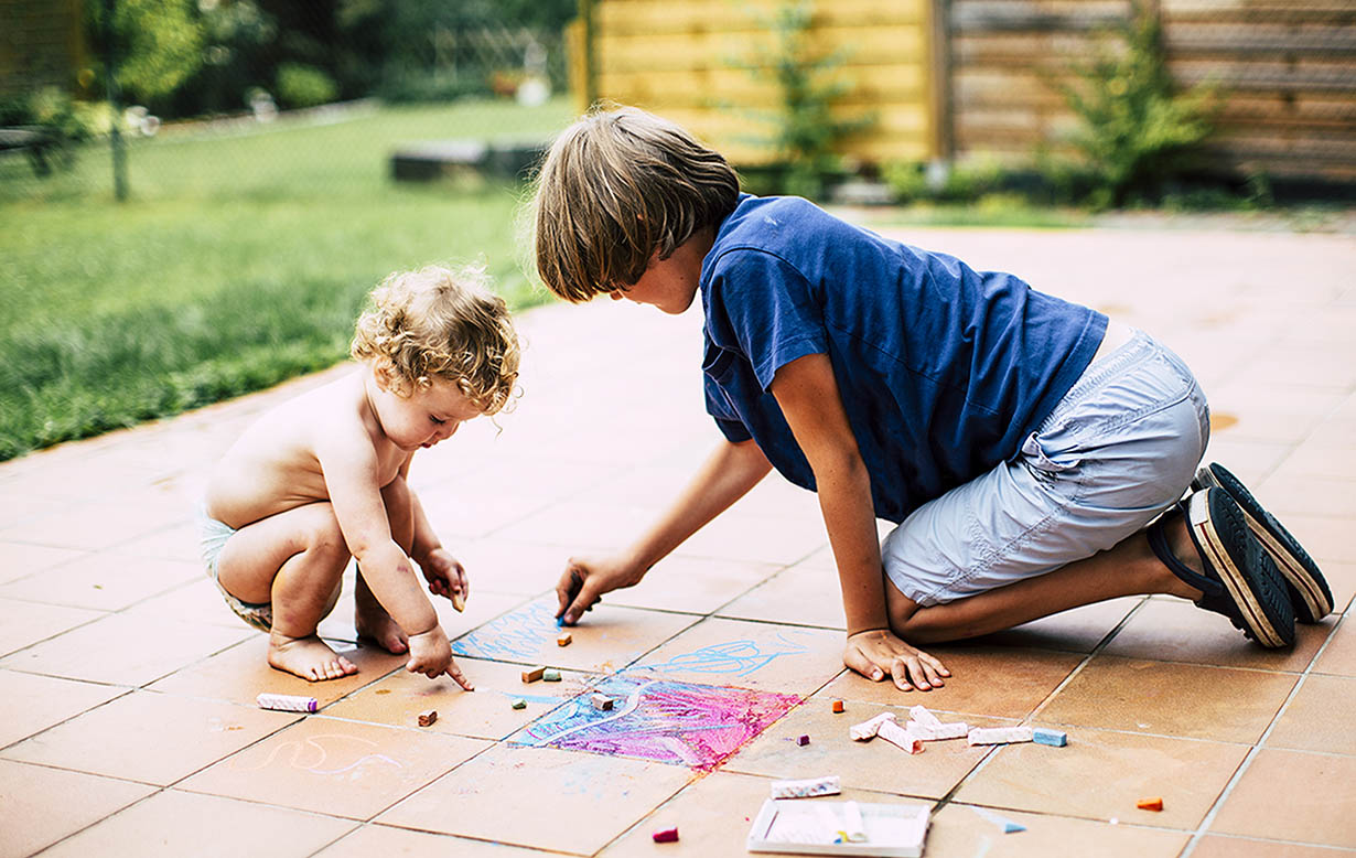 Young boy playing with his baby sister, both are writing with chalk on their deck.
