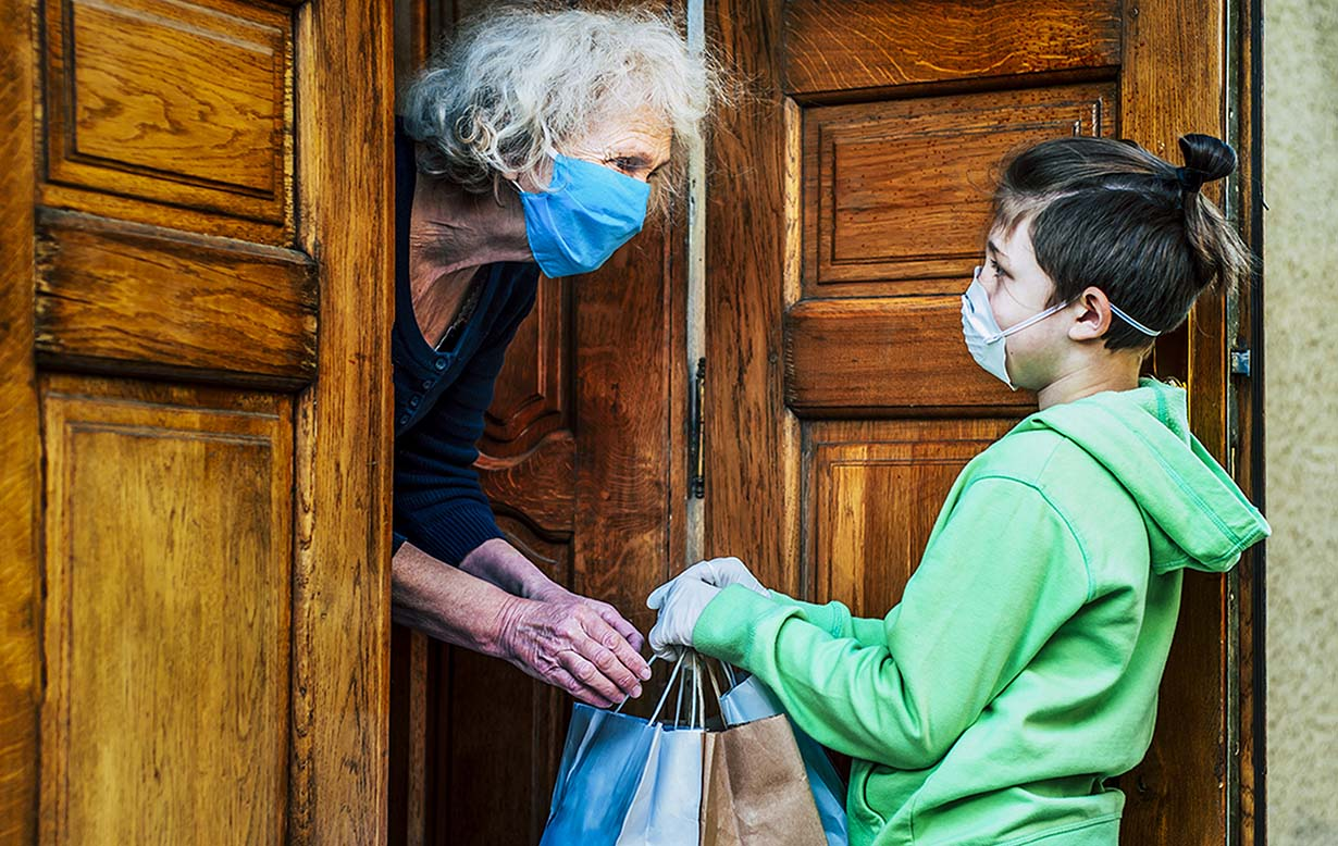 Practicing proper social distancing, a younger boy wears gloves and a mask while delivering groceries to an elderly lady, also wearing a mask.