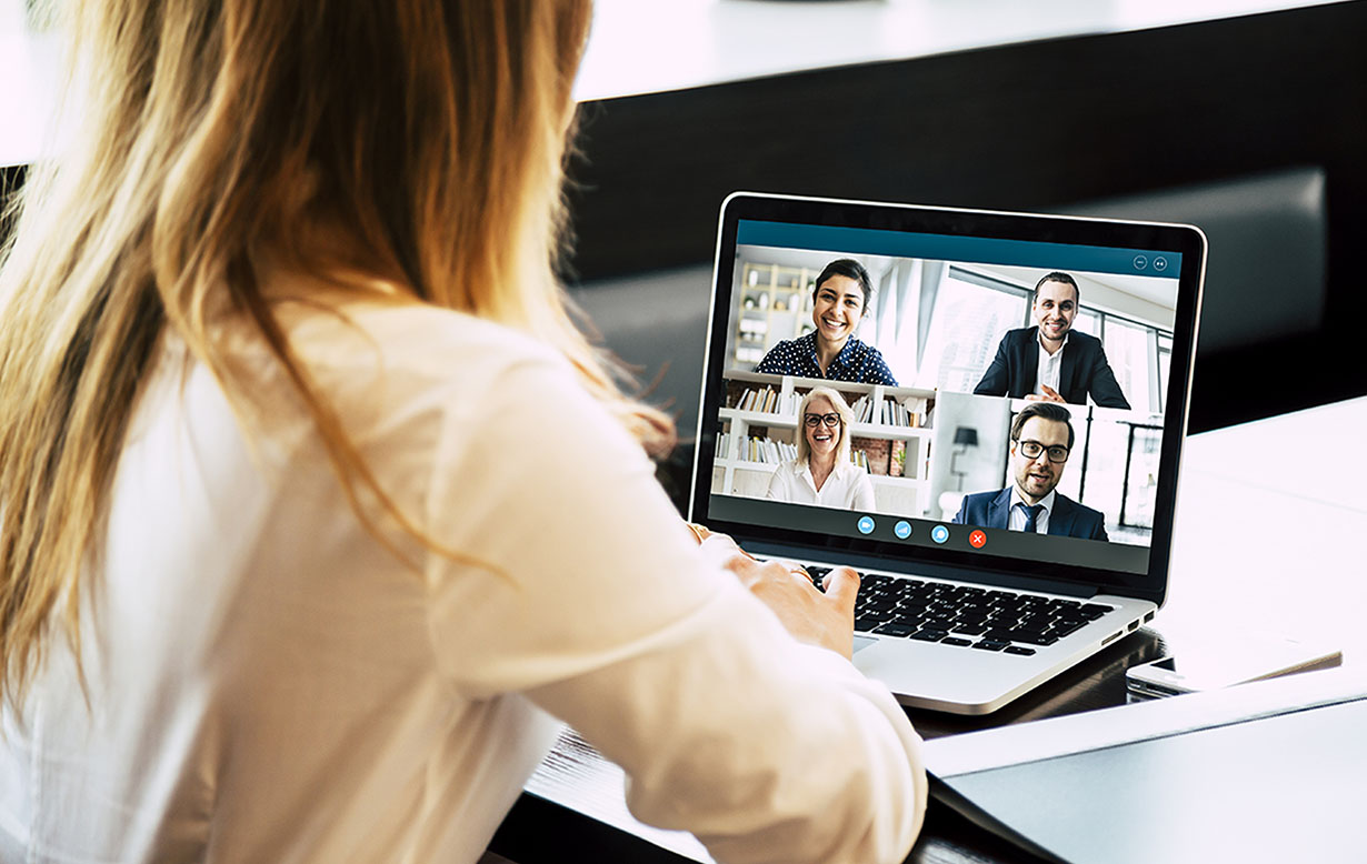 Woman practicing proper social distancing by teleconferencing with four individuals on her laptop.
