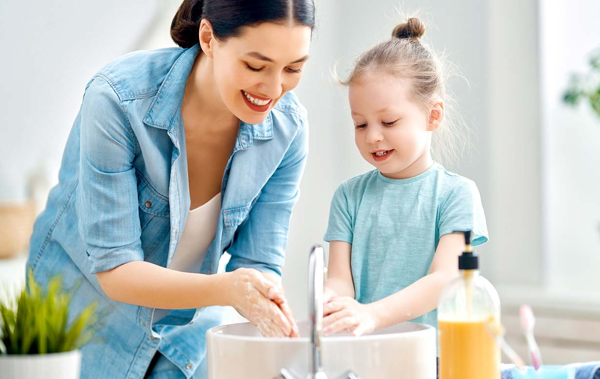 Woman teaching her young daughter how to wash her hands.