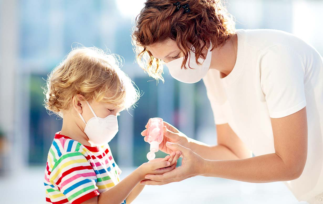 Woman wearing a mask giving her young son (also wearing a mask) some hand sanitizer.