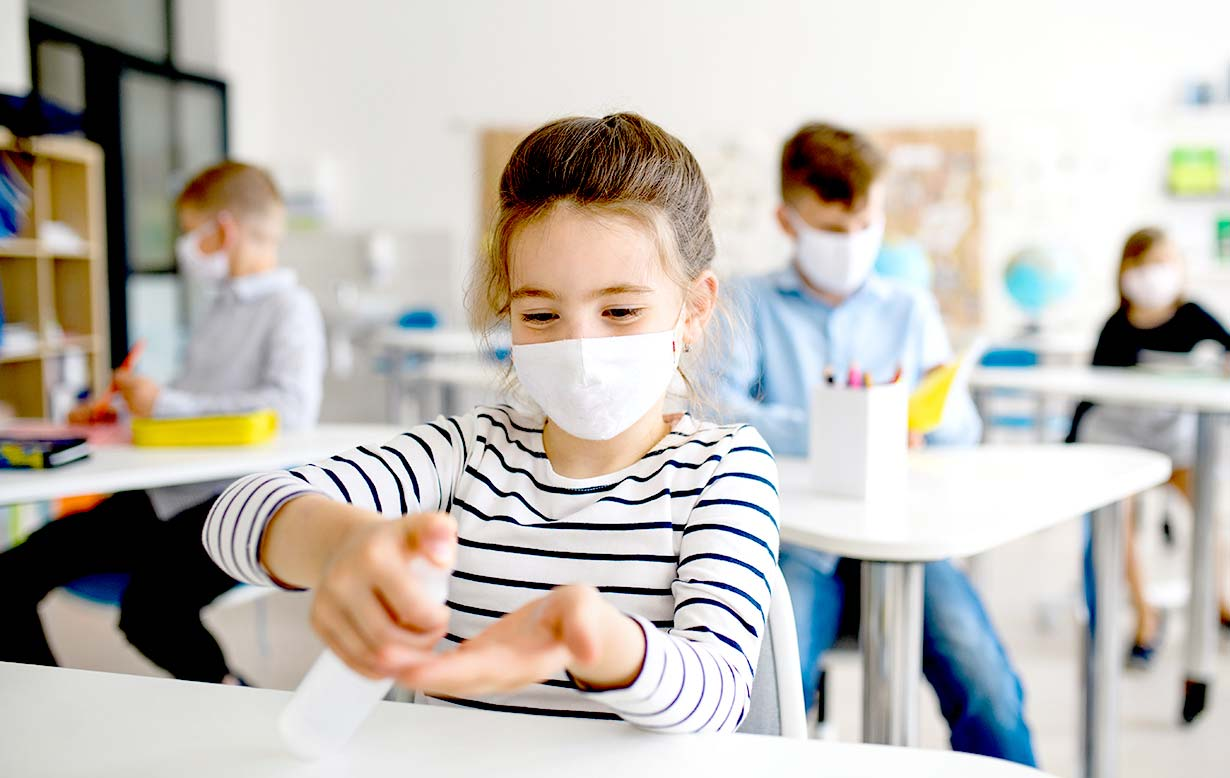 Young girl wearing a mask in classroom using hand sanitizer. Other kids in background are also wearing masks.