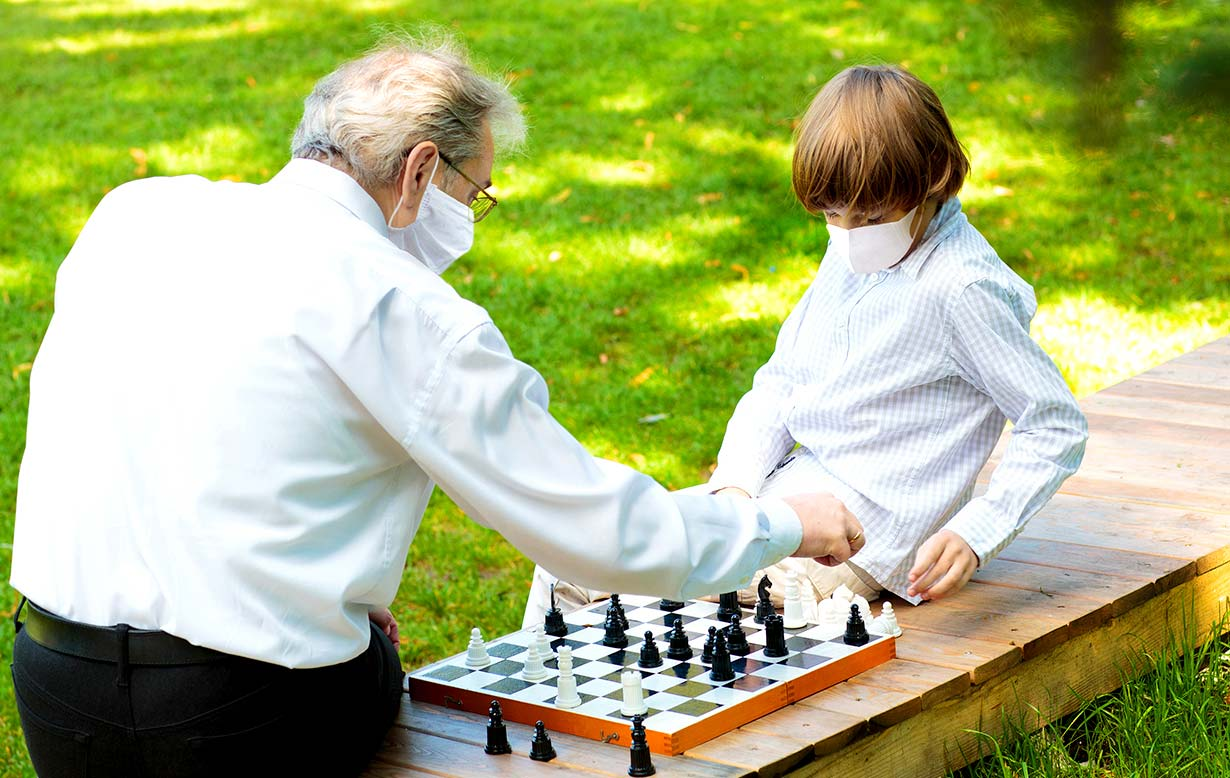 Grandfather and grandchild (both wearing masks) outside in the park, playing chess.