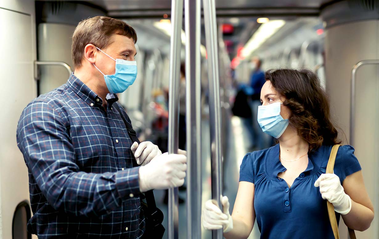 A man and woman, both wearing masks and gloves, on talking to each other on mass transit.
