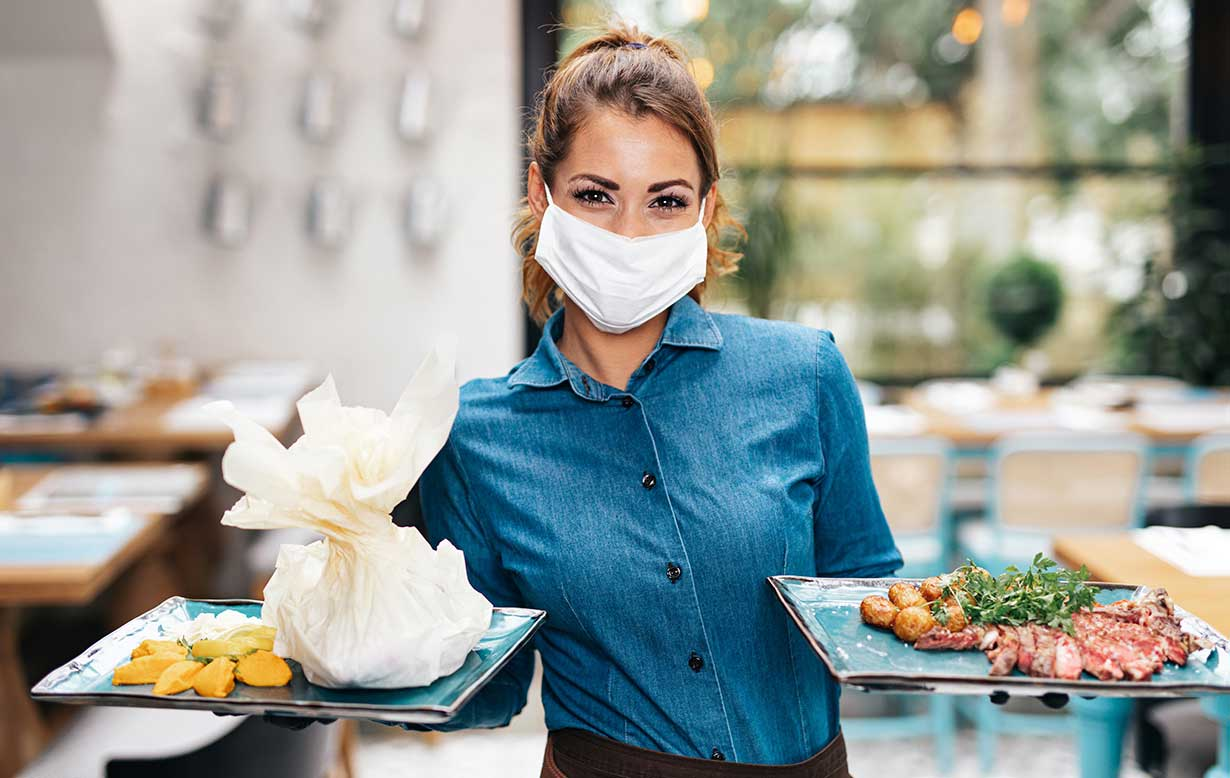 Female server wearing a face mask while holding plates of food.
