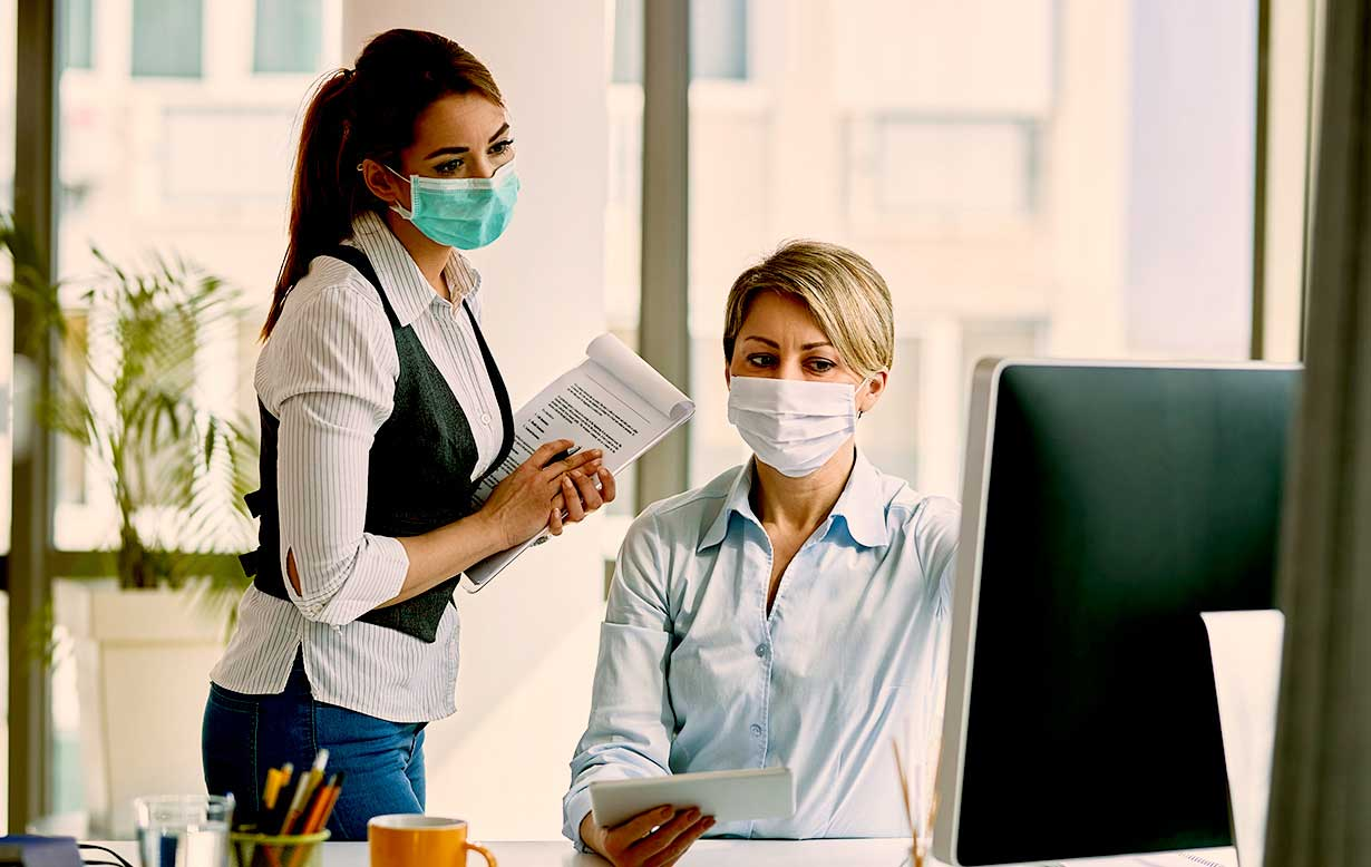 Two office workers wearing masks while in close proximity.