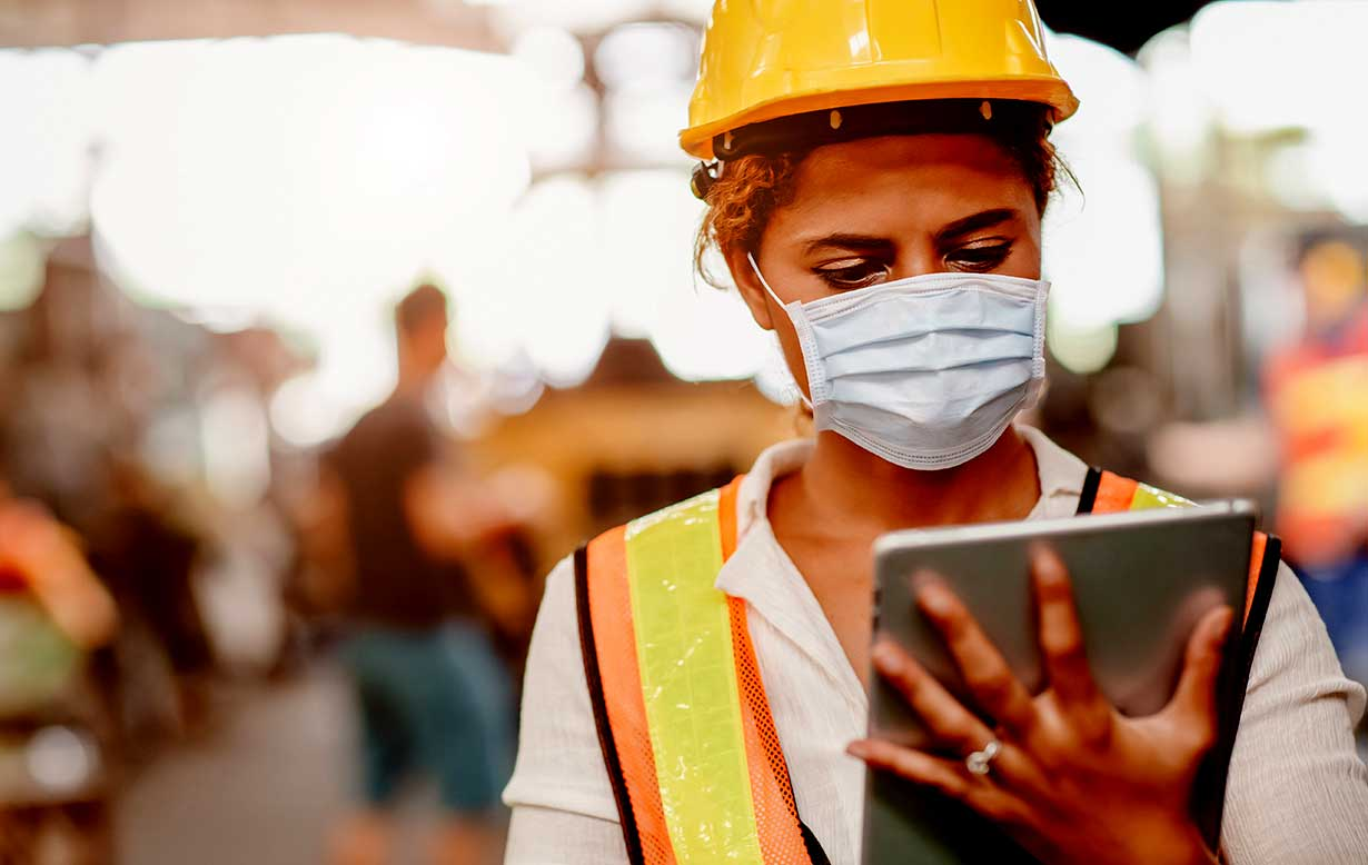 Female construction worker wearing a face mask while outdoors.