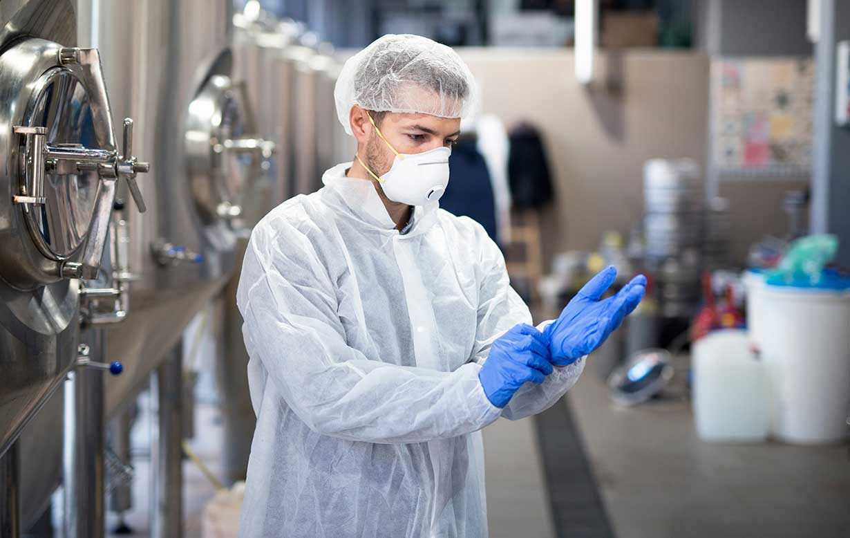 Male factory worker wearing disposable isolation suit, hair net, N95 face mask and putting on disposable nitrile gloves.